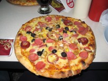 A pizza pockmarked with olives.